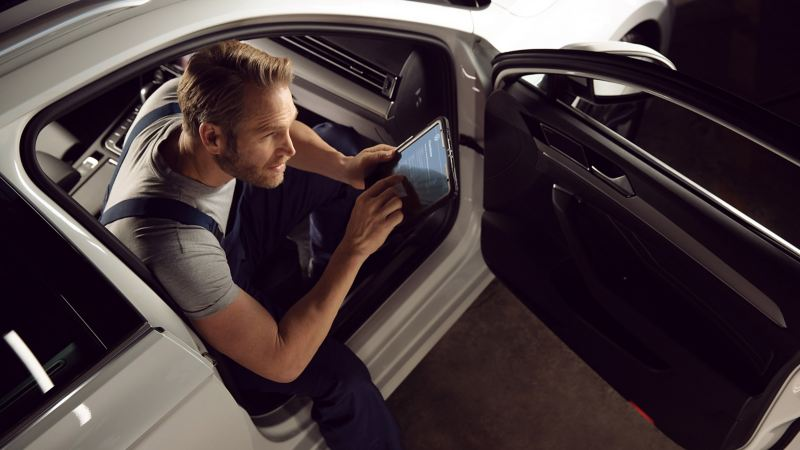 A car mechanic using a tablet device in a car