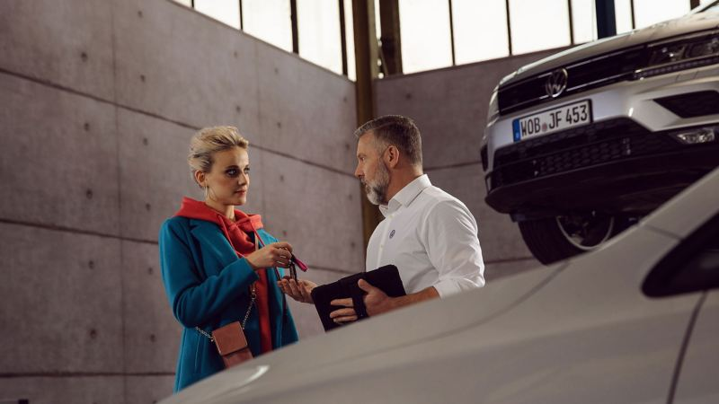 A car owner handing her car keys to a service representative