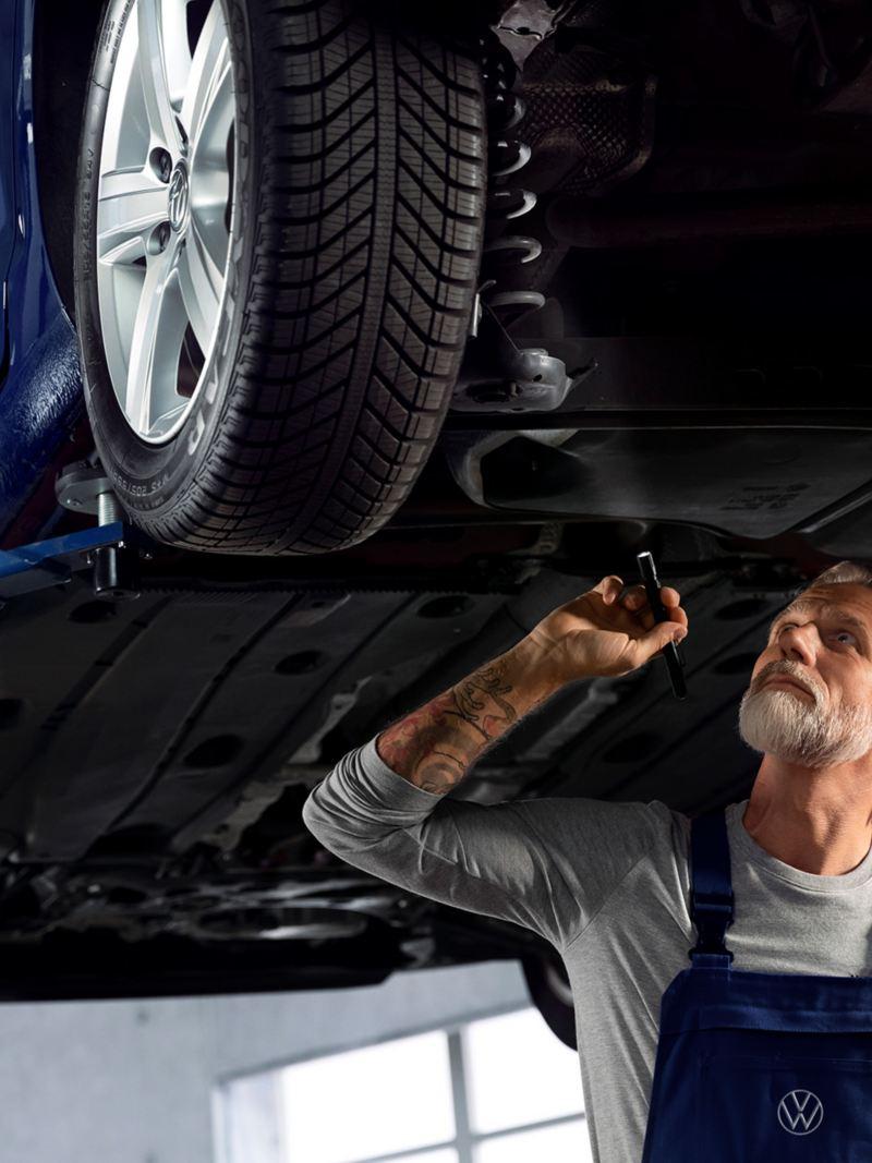 Ein Mechaniker arbeitet an einem blauen VW.
