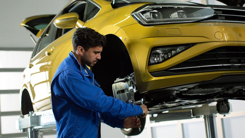 A car mechanic servicing a car