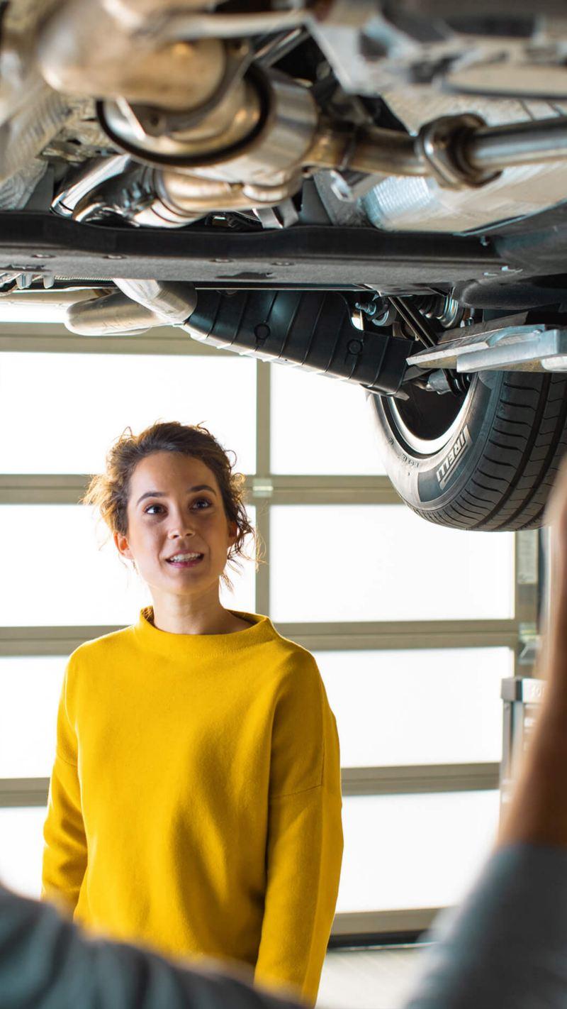 A customer and a Volkswagen mechanic standing under a car