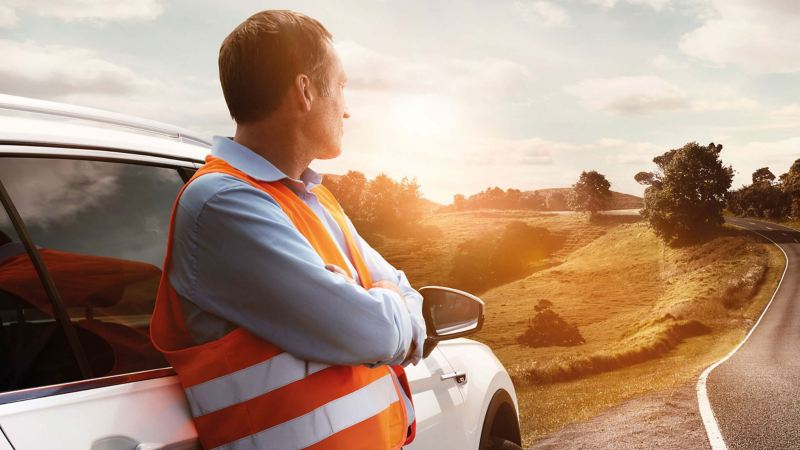 A man wearing a high viz waistcoat leaning against a car on a roadside