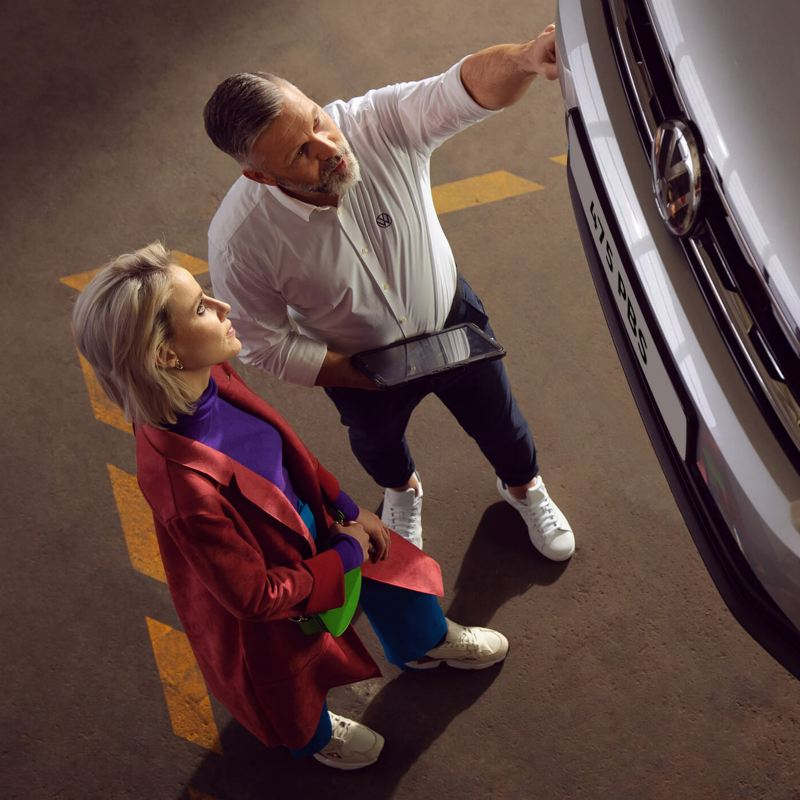 A customer and a Volkswagen service personnel looking at the body of a car