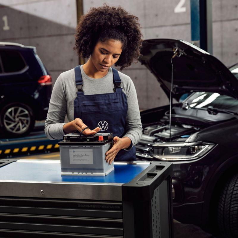 A Volkswagen service employee handling a battery