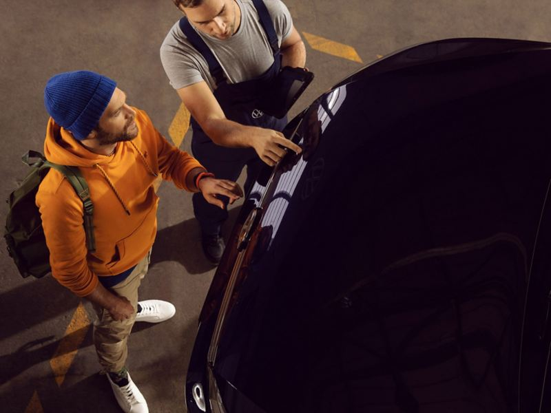 A customer and a Volkswagen service personnel looking at the front of a car