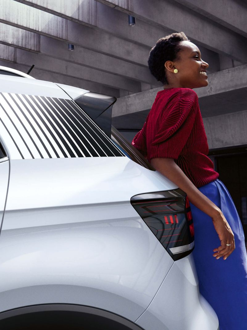 A woman leaning on the back of a Volkswagen vehicle