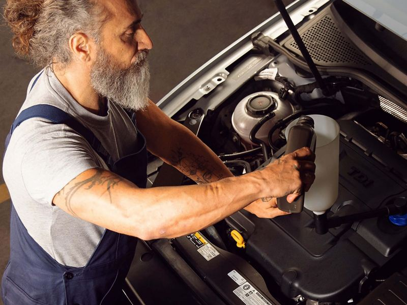 A Volkswagen service employee using the right engine oil for a Volkswagen vehicle