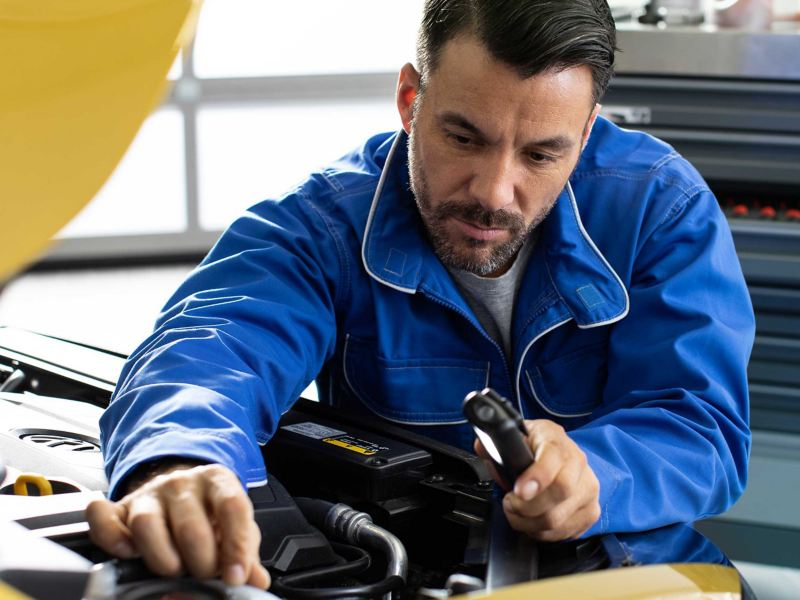 A Volkswagen mechanic checking inside the bonnet of a car