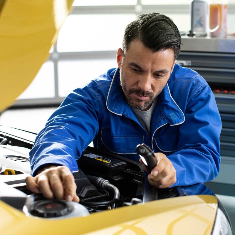 A Volkswagen mechanic checking inside the bonnet of a car