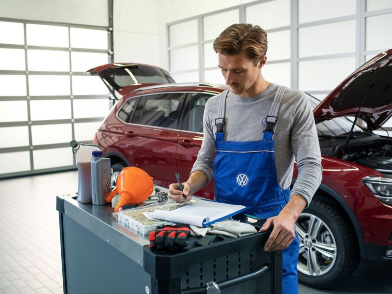 A Volkswagen service employee writing notes at a repair centre