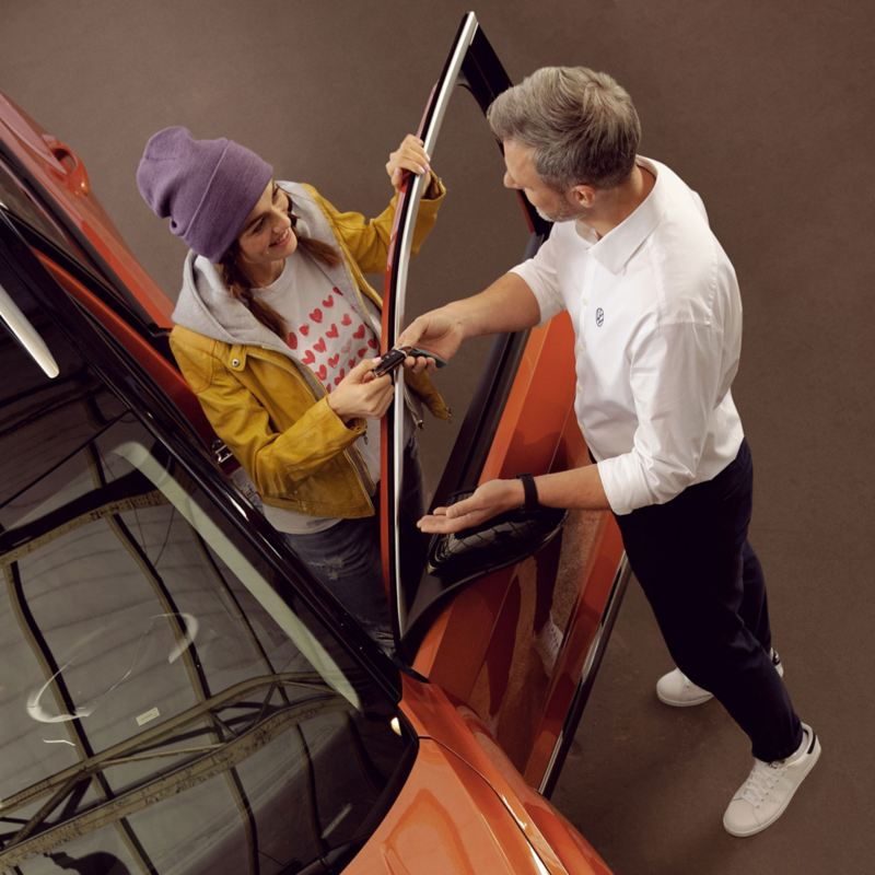 A Volkswagen service employee handing keys to a customer