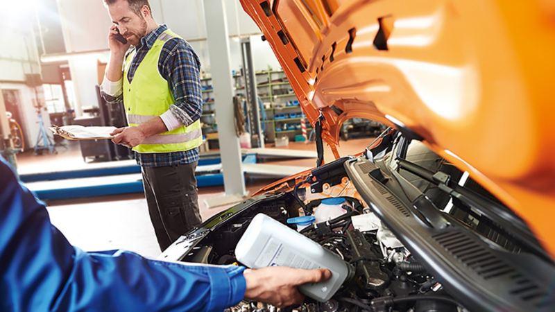 Un meccanico sta rabboccando i liquidi di un veicolo.