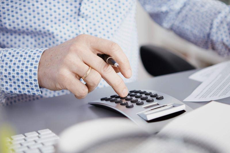 Dealer in VW van centre with calculator on desk