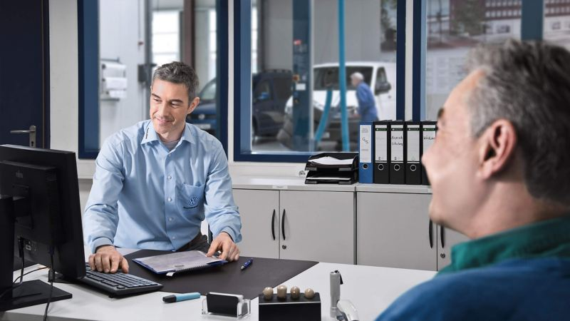 VW dealer and customer purchasing a car