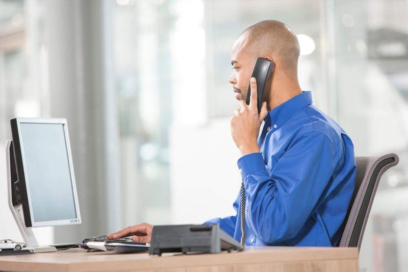 Car dealer at desk on phone