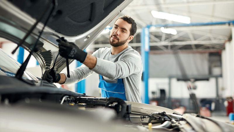 VW mechanic inspecting engine at free service