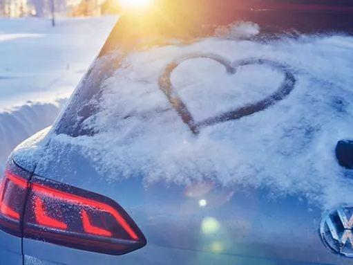 Un coeur dessiné avec de la neige sur la fenêtre d'une Volkswagen