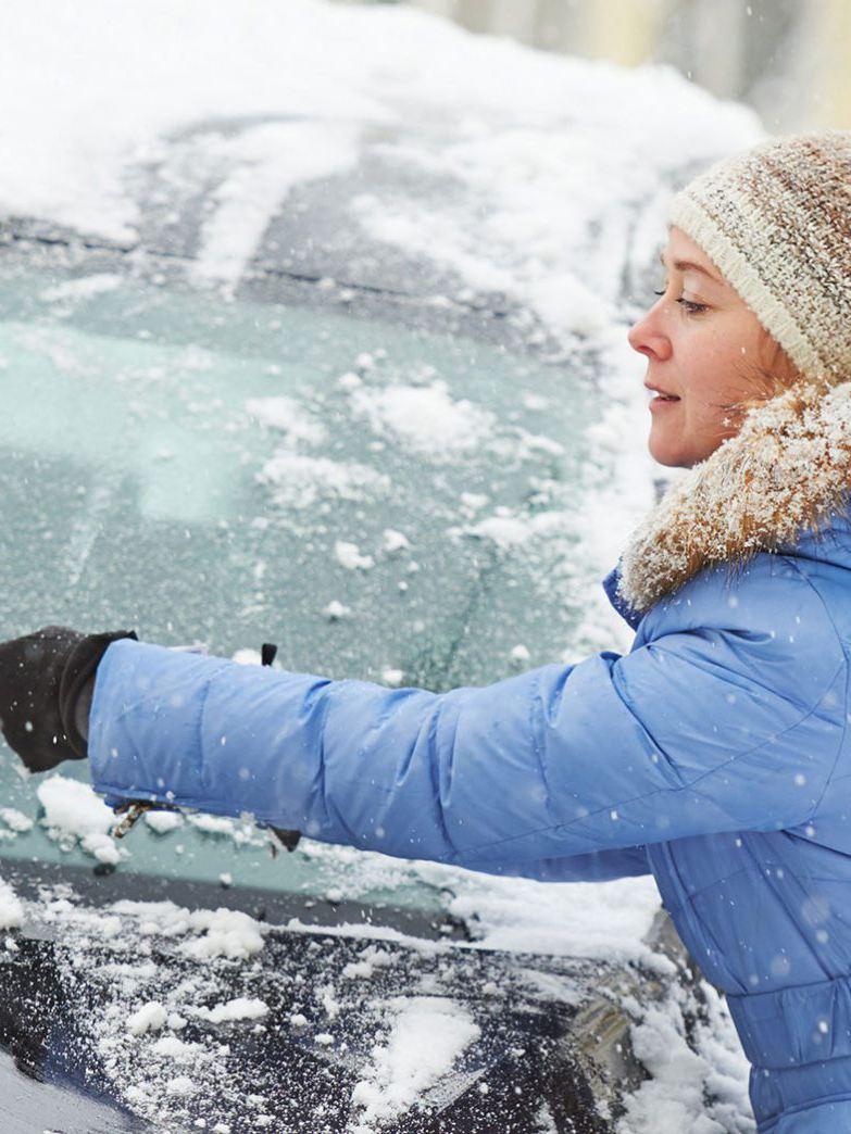 Kvinna tar bort snö från vindrutan på bil