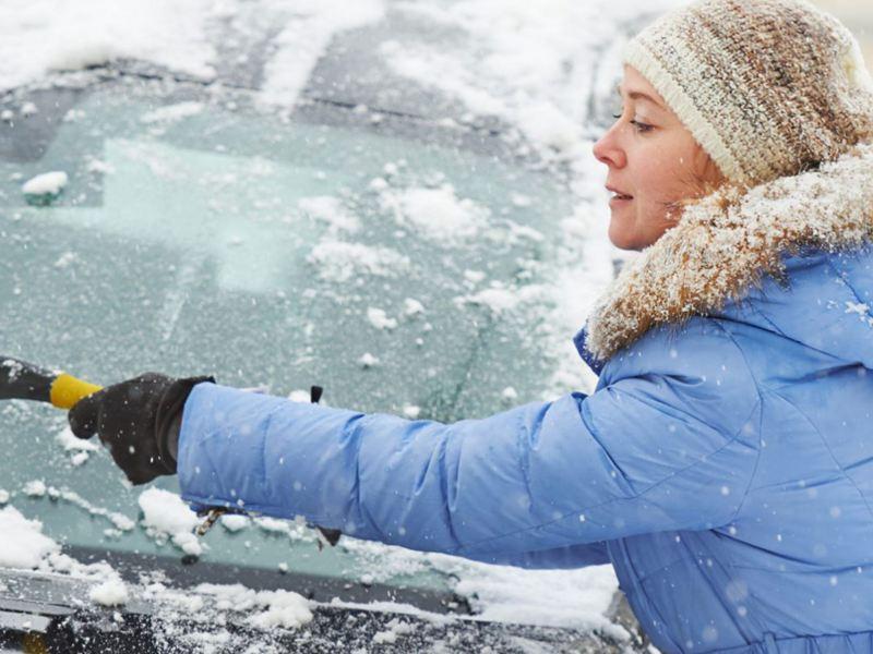 Kvinna som tar bort snö från bilrutan