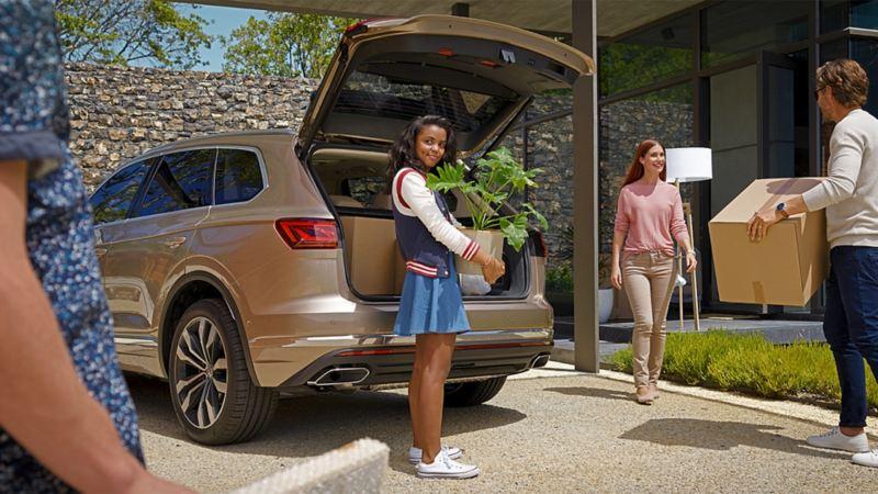 Ein Mädchen steht hinter einem VW Touareg und hält eine Einkaufstütte