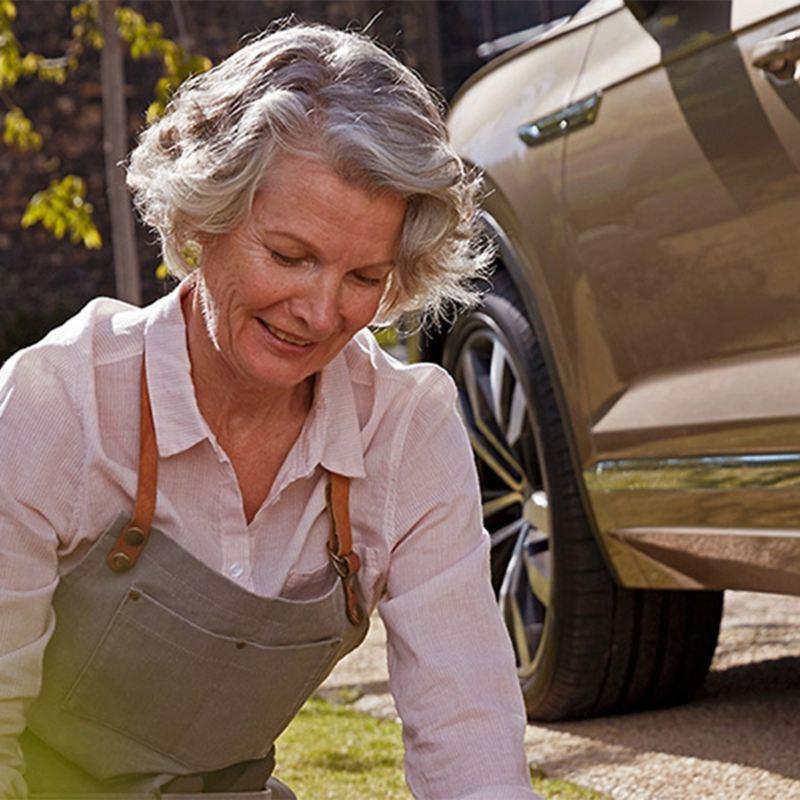 Ältere Frau im Garten vor Fahrzeug – Leasing-Angebote