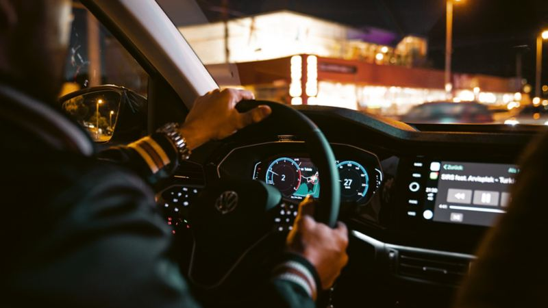 Förare talar i telefon med båda händerna på ratten