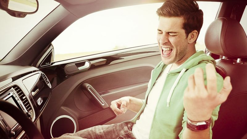 Man lyssnar på musik och spelar luftgitarr inuti bil
