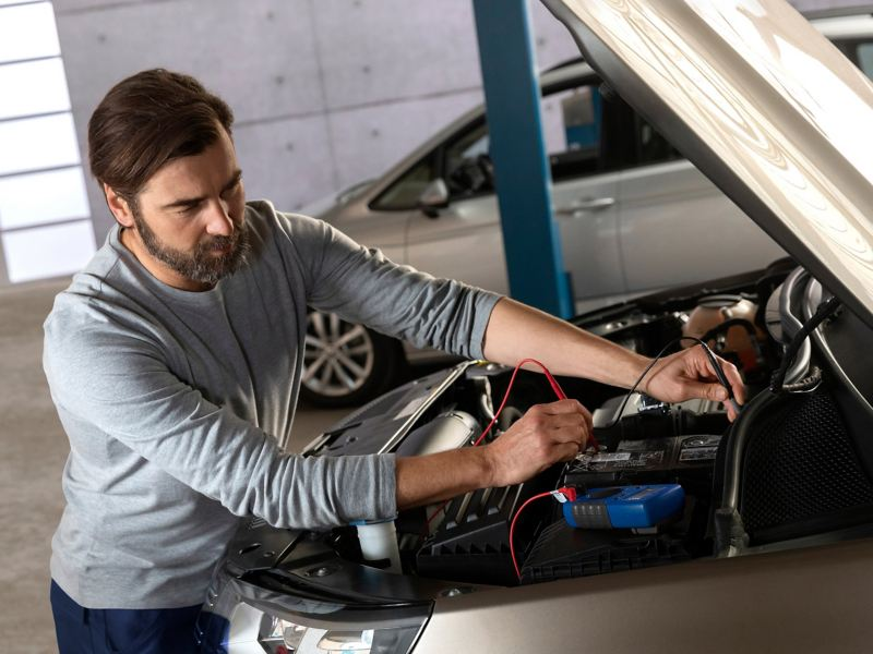 A male mechanic working on a car battery