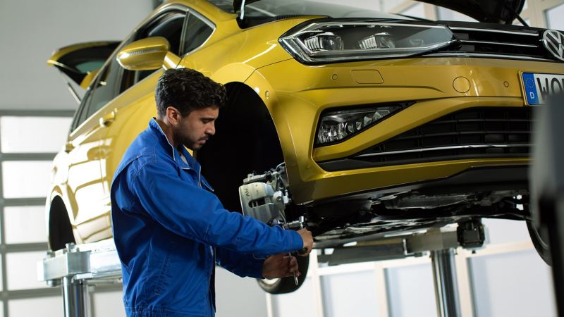 A Volkswagen technician working on car