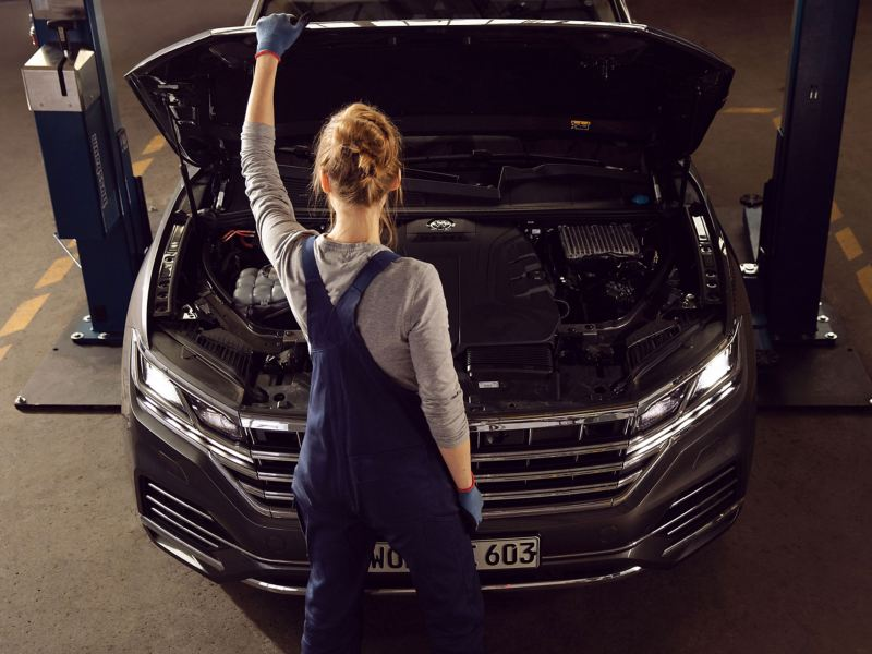 A Volkswagen service employee holding onto an opened car bonnet