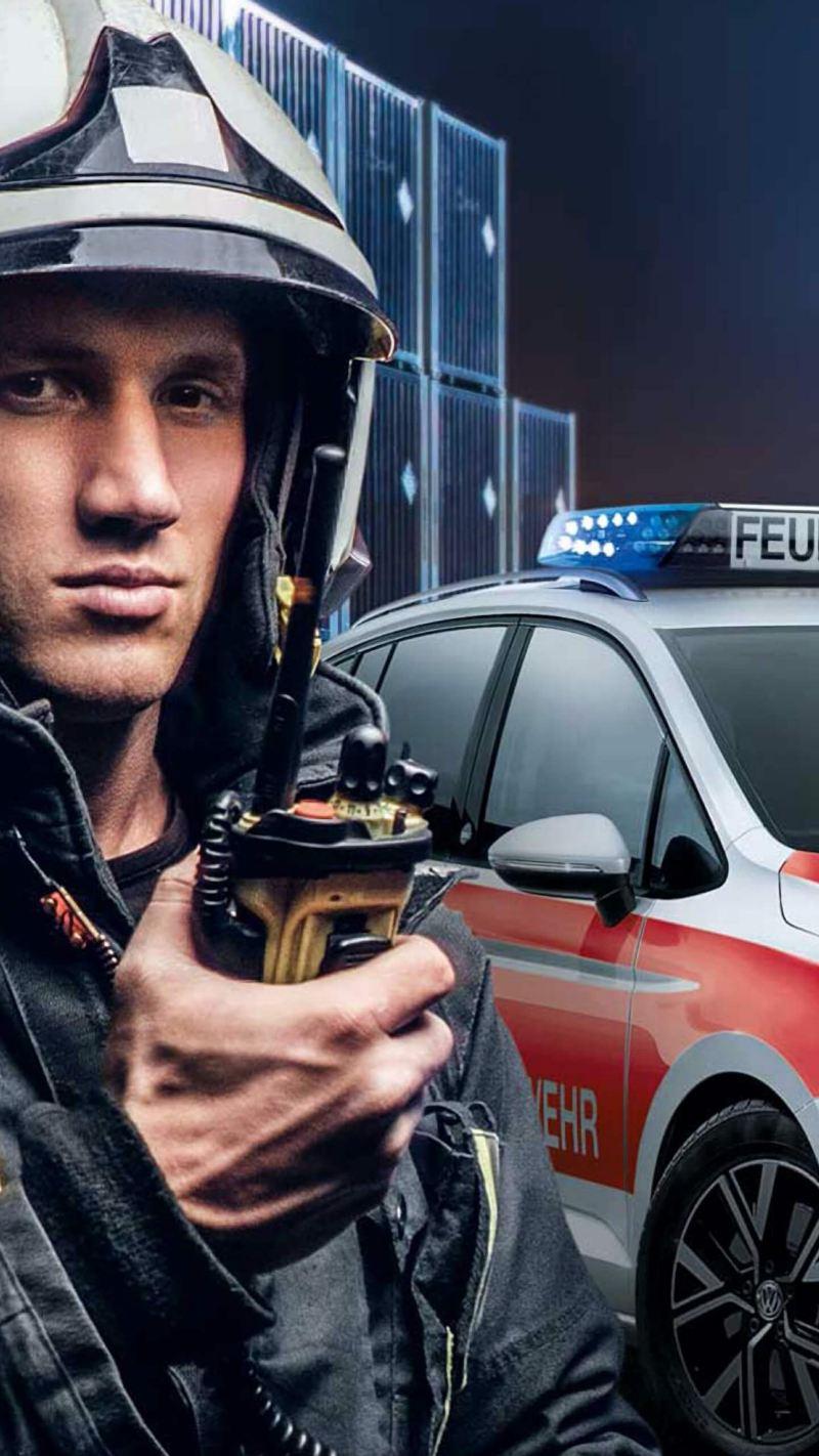Ein Feuerwehrmann am Einsatzort, im Hintergrund ein Feuerwehrauto von Volkswagen