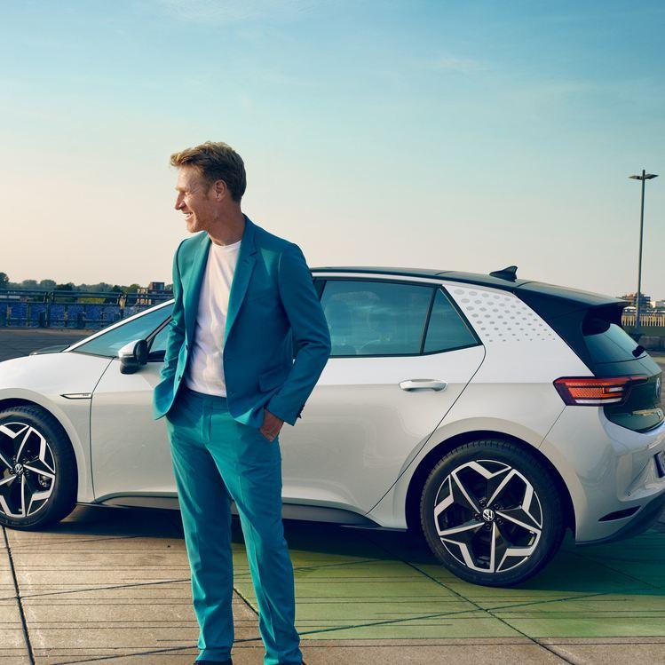 Ein Mann in einem hellblauen Anzug steht vor einem Volkswagen ID.3 1st Edition in der Farbe Glacier White Metallic.