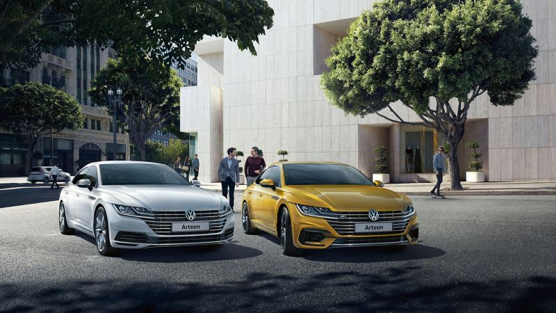 A yellow and a silver Volkswagen Arteon parked in front of a building, surrounded by tree's and pedestrians.