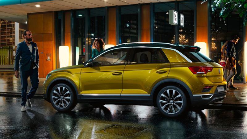 giovani intorno a VW T-Roc parcheggiata in città di notte