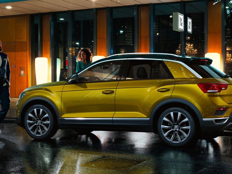 Un uomo davanti a Volkswagen T-Roc di notte parcheggiata davanti a negozi