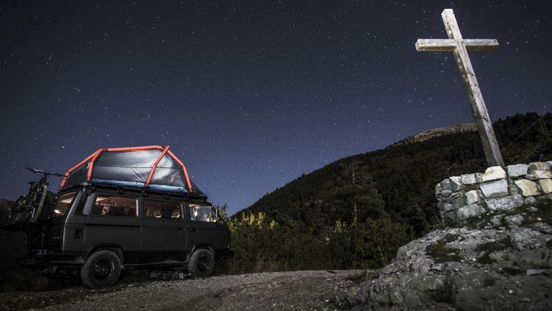 Rob Herans T3 steht nachts mitten in einer wilden Berglandschaft. Im Vordergrund ist das Gipfelkreuz zu sehen.