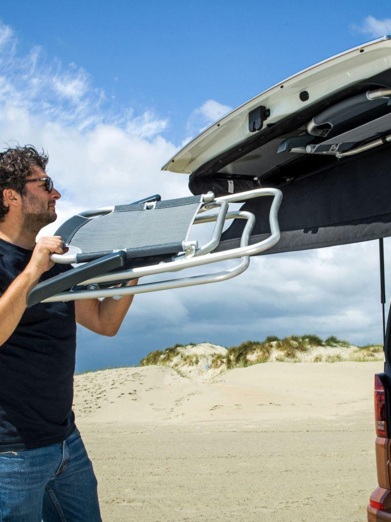 Mężczyzna pakuje leżak do klapy bagażnika Nowej Californii 6.1