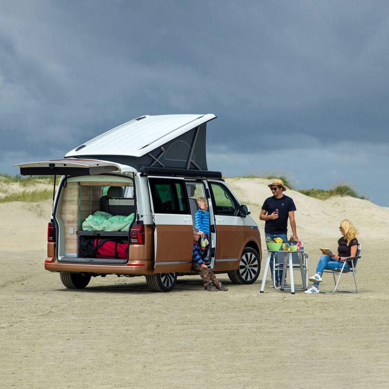 Na piaszczystym podłożu stoi Nowa California 6.1 z rozłożonym dachem i otwartym bagażnikiem a obok niej jest czteroosobowa rodzina