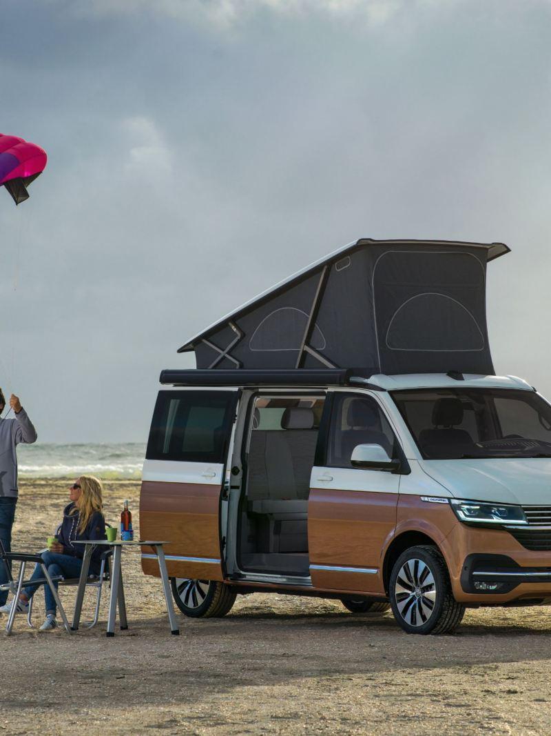Kobieta i mężczyzna na plaży przed California 6.1 z rozłożonym namiotem dachowym