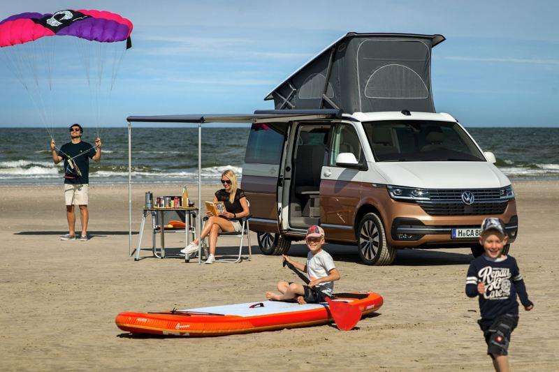 Rodzina bawi się na plaży, obok stoi Nowa California 6.1 z rozłożonym dachem sypialnym i markizą