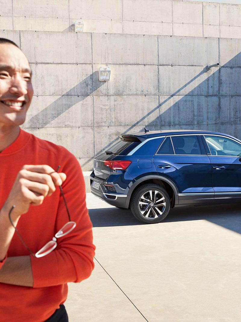 Man in front of Volkswagen T-Roc UNITED in front of concrete wall