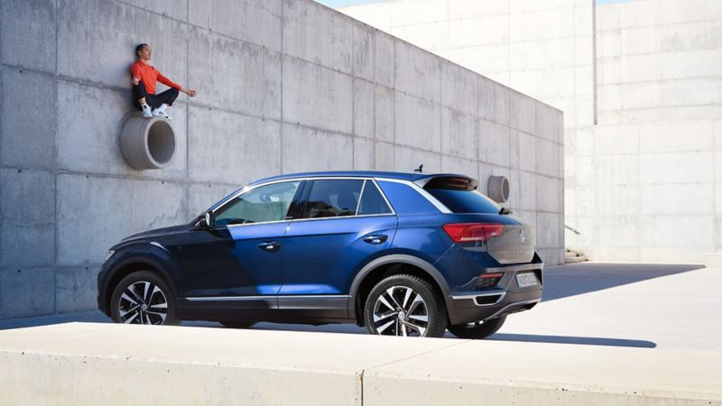 3/4 rear view of Volkswagen T-Roc UNITED in front of concrete wall, man sitting on a tube.