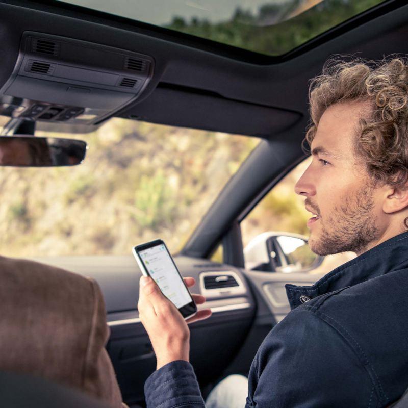 Un uomo a bordo di un'auto Volkswagen consulta il suo smartphone.
