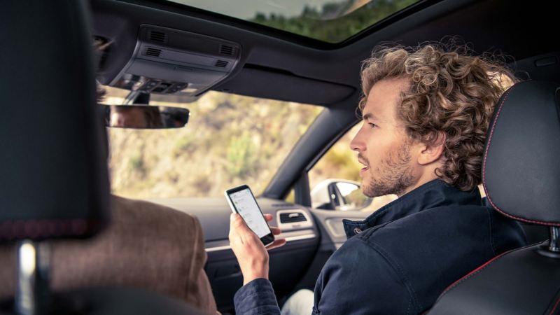 interno auto uomo con smartphone lato passeggero che parla con guidatore