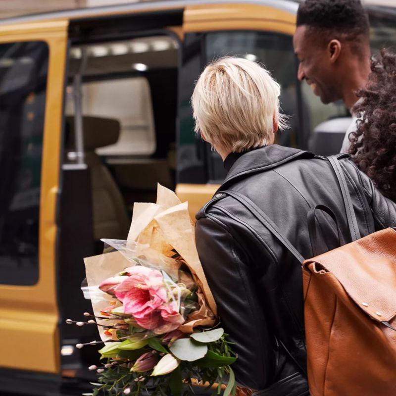 Chica con un ramo de flores vista de espalda caminando hacía una furgo