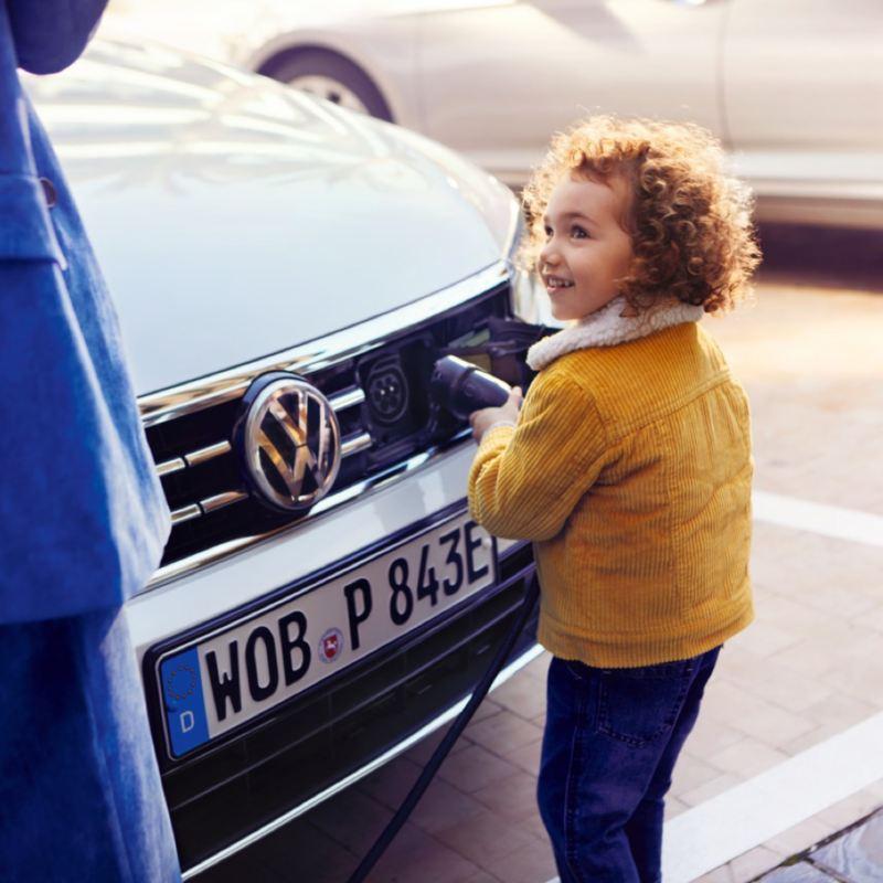 Niña sujetando un enchufe de carga eléctrica frente a un Volkswagen Passat GTE blanco