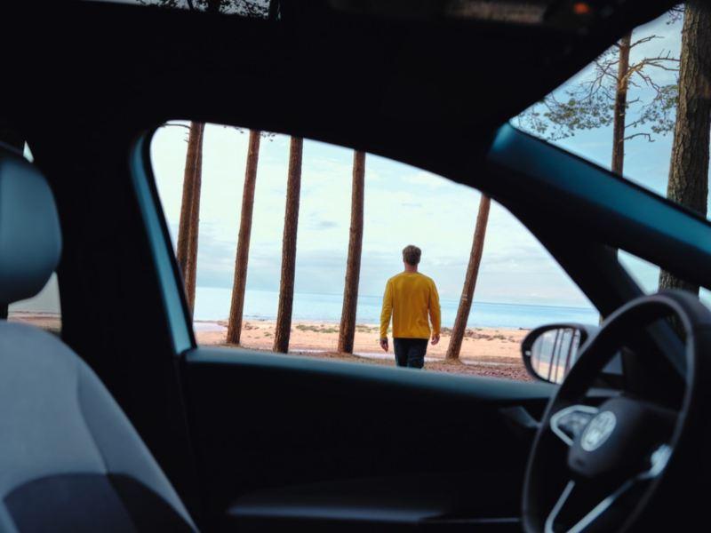 Hombre de espaldas caminado hacia el mar visto desde el interior de un Volkswagen
