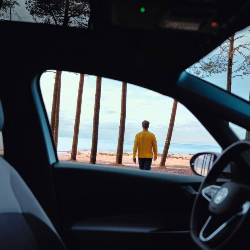 Chica tapándose los ojos del sol con la mano frente a un Nuevo Volkswagen ID.3 blanco