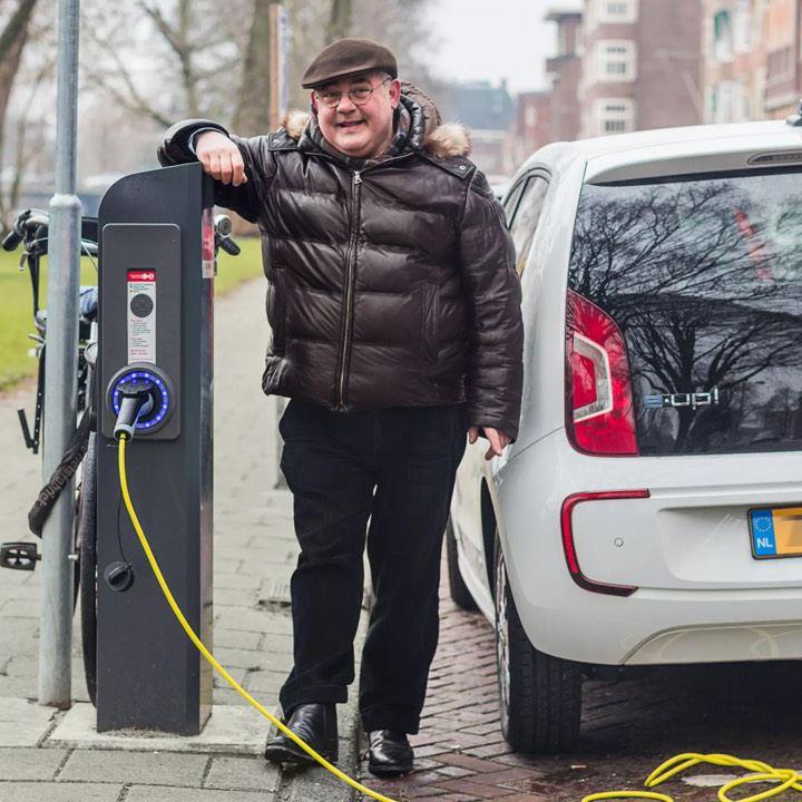 Hombre mirando la cámara cargando un e-Up! de Volkswagen en la calle