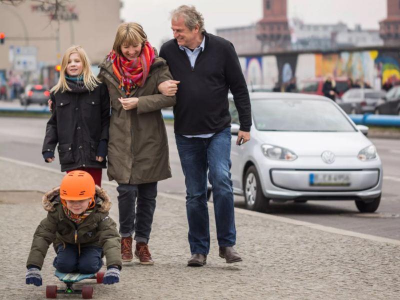 Familia paseando por la ciudad de Berlin con un Volkswagen e-up! blanco de fondo